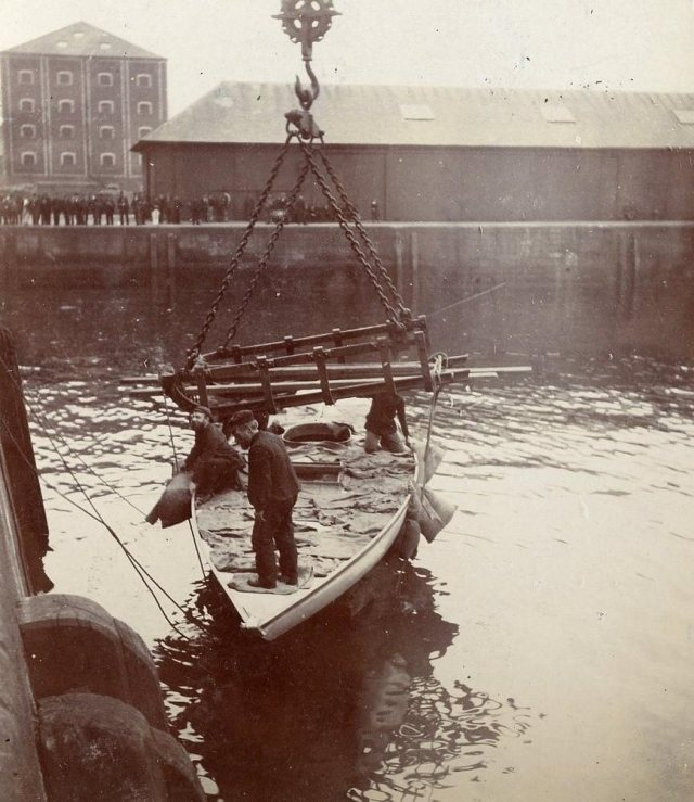 Mimine (2½-Rater) launching, 1894. Could the man on the  foredeck be Orr himself? Note the iron sledge in use  as a spreader bar to prevent the lifting slings from  squeezing her topsides and rail - what was its day job? (McLean Museum and Art Gallery, Inverclyde Council)